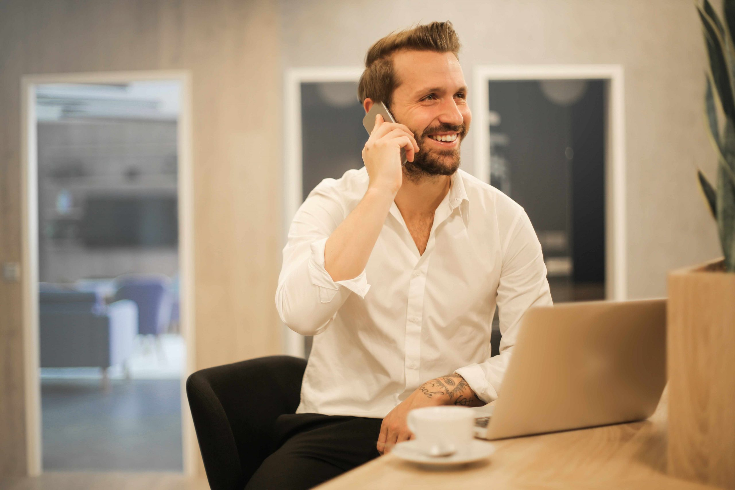 Smart working - uomo davanti a pc al telefono sorridente