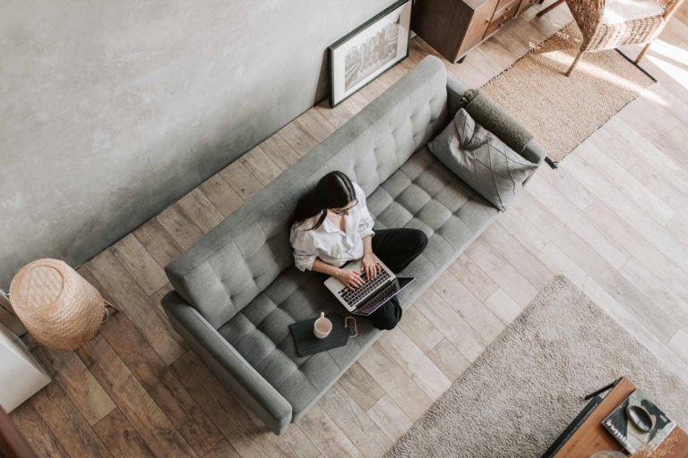 Smart Working procedura semplificata - donna lavora in smar working su divano veduta dall'alto